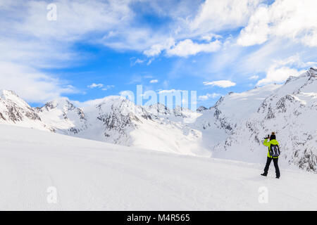 Unidentified woman skier taking picture with smart phone of beautiful mountains during winter season, Obergurgl - Stock Photo
