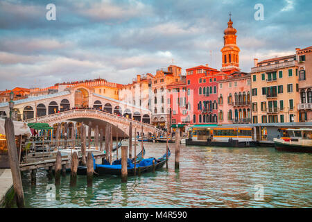 Classic panoramic view with traditional Gondolas on famous Canal Grande with famous Rialto Bridge in the background - Stock Photo