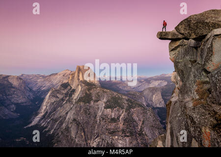 A fearless male hiker is standing on an overhanging rock at Glacier Point enjoying the breathtaking view towards - Stock Photo