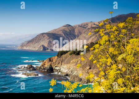 Scenic view of the rugged coastline of Big Sur with Santa Lucia Mountains and Big Creek Bridge along famous Highway - Stock Photo