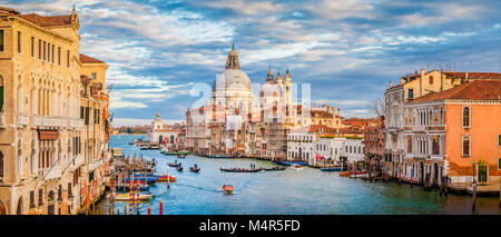 Classic panoramic view of famous Canal Grande with Basilica di Santa Maria della Salute in beautiful golden evening - Stock Photo