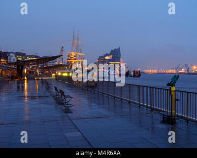 Hamburg, Germany - April 04, 2016: Deserted port of Hamburg at rainy day in the evening with Elbphilharmonie and - Stock Photo