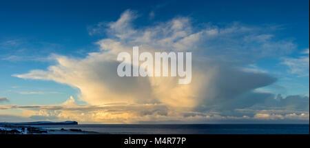 Cumulonimbus cloud near sunset over Dunnet Head and the Pentland Firth, from near St. John's Point, Caithness, Scotland, - Stock Photo