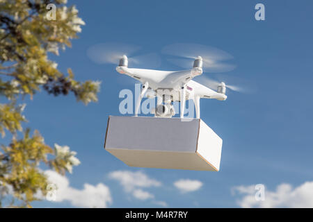 Unmanned Aircraft System (UAS) Quadcopter Drone Carrying Blank Package In The Air. - Stock Photo