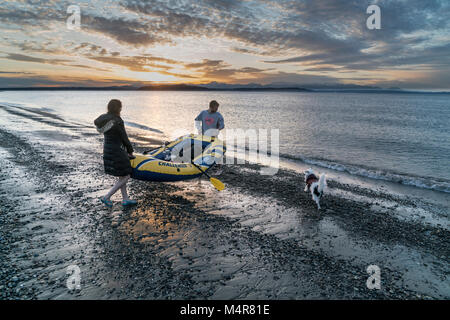 A couple launching an inflatable reft at sunset off Alki Beach, Seattle, Washington, USA - Stock Photo