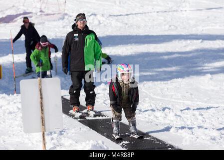 Kids and ski instructor on a magic carpet ski lift at Anthony Lakes Mountain Resort in Northeast Oregon. - Stock Photo