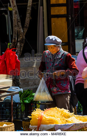 The Friday market, where local Yi and Bai minorities come to buy and sell their wares in the historic market town - Stock Photo