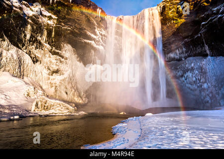 Skogafoss waterfall in Iceland behind a spectacular rainbow - Stock Photo