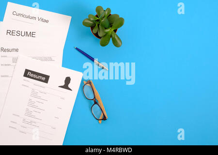 Pile of cv papers application form on a blue desktop.Top view - Stock Photo