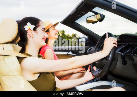 Close-up open interior of modern luxury sports roadster car with two young woman enjoying freedom and life style - Stock Photo