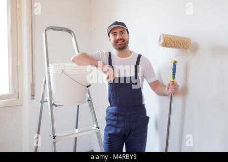 Man ready to paint a wall holding painting tools - Stock Photo