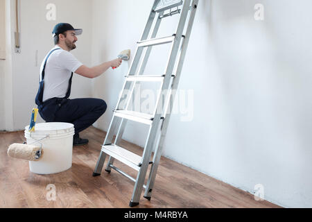 Professional painter worker is painting a wall - Stock Photo