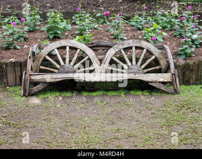 Wooden bench which made from the old cart wheel in the flower row of the botanical garden. - Stock Photo