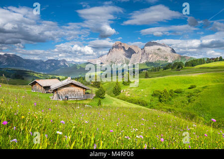 Beautiful view of idyllic alpine mountain scenery with traditional old mountain chalets and fresh green meadows - Stock Photo