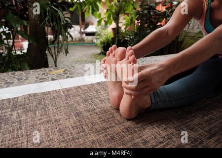 Detail of caucasian woman doing yoga asana exercises. Girl do sitting forward bend pose. Healthy lifestyle outside - Stock Photo