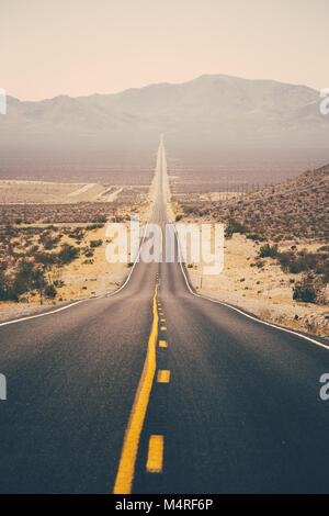 Classic panorama view of an endless straight road running through the barren scenery of the American Southwest - Stock Photo