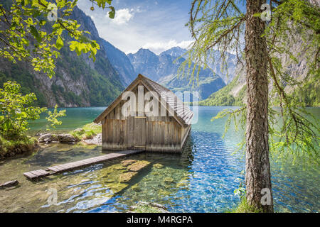 Traditional wooden boat house at the shores of famous Lake Obersee in Nationalpark Berchtesgadener Land on a sunny - Stock Photo