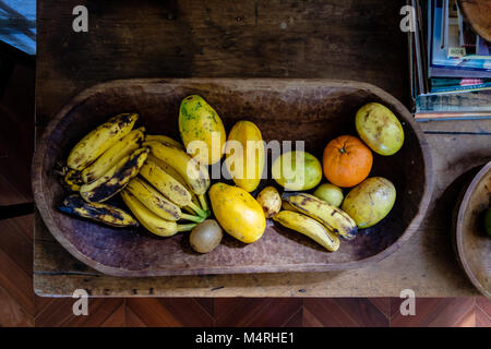 various fruits on a wooden platter with incoming sunlight. There are bananas, oranges, papaya - Stock Photo