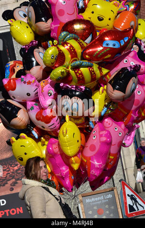 a lady or woman femail selling helium filled childrens toys balloons in a town centre shopping are of a city. colourful - Stock Photo