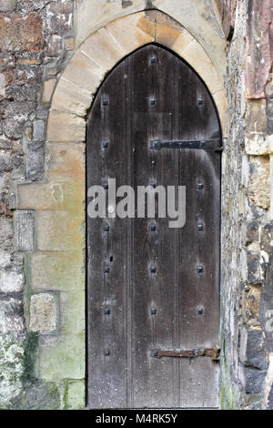 ... An old historic wooden castle or dungeon door in a stone wall made of thick wood & old iron lock in iron studded old oak door to the lock up Lacock ...