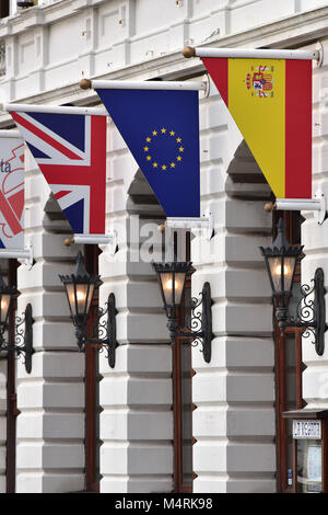 The Spanish, European and British or English flags and banners hanging above the entrance to a Spanish or European - Stock Photo