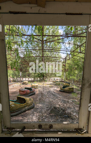 Looking out from the kiosk at the iconic dodgem cars in Luna Park, Pripyat, Chernobyl, Ukraine - Stock Photo