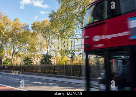 Red London bus on Theobalds Road in front of trees in Grays Inn Gardens, London, UK - Stock Photo