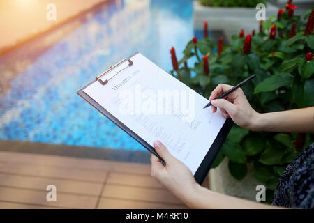 close-up portrait of woman fills out visa application form in Iceland against pool background.. Front used with - Stock Photo