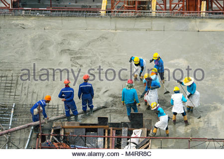 Construction worker Concrete pouring during commercial concreting floors of building in construction site and Civil - Stock Photo