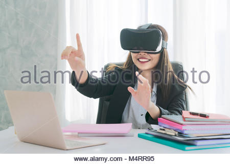 Future is right now. Confident young woman adjusting her virtual reality headset and smiling while sitting at her - Stock Photo