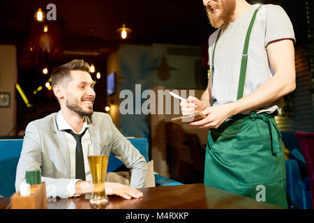 Cheerful bearded man wearing stylish suit sitting at cafe table and making order, red-haired waiter wearing apron - Stock Photo