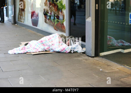 Manchester, UK. 17th Feb, 2018. Homelessness has increased due to housing costs. A homeless person lying down under - Stock Photo