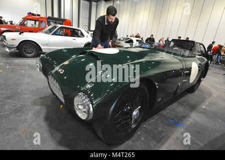 A man polishing a 1955 Jaguar XK140 Special racing car on display at the London Classic Car Show which is taking - Stock Photo