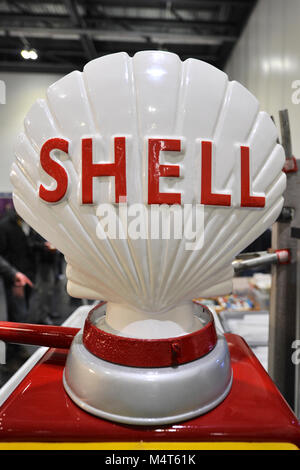An Shell sign on top of a vintage petrol pump on display at the London Classic Car Show which is taking place at - Stock Photo