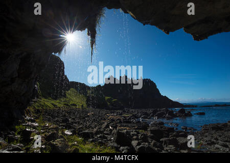 Silhouette of Dunluce Castle from inside a sea cave, Causeway Coast, County Antrim, Northern Ireland. - Stock Photo
