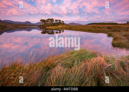 Sunset reflections in Derryclare Lough, Connemara, County Galway, Ireland. - Stock Photo