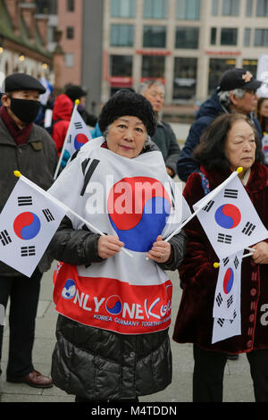 Frankfurt, Germany. 17th Feb, 2018. An older woman wears a cape with the Korean flag on it and holds two Korean - Stock Photo
