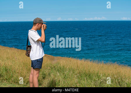 A young man taking photos near the ocean with an analogue SLR camera