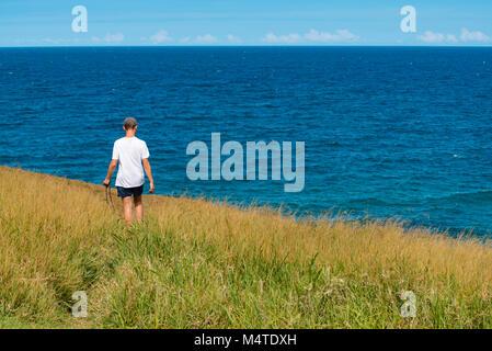 A young man walking along a narrow path through long grass near the ocean with an analogue SLR camera - Stock Photo