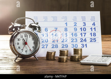 Tax Time On Alarm Clock With Coins, Calculator And Calendar Over The Wooden Table - Stock Photo