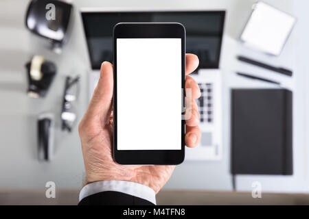 Close-up Of A Businessperson's Hand Showing Smart Phone Blank Screen In Office - Stock Photo