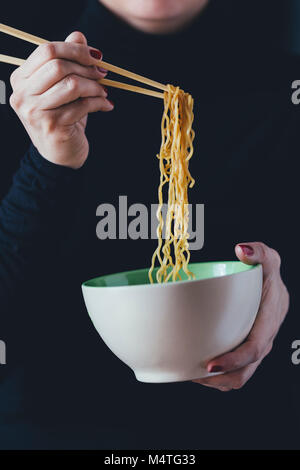 Woman holds a bowl of noodles with chopsticks - Stock Photo