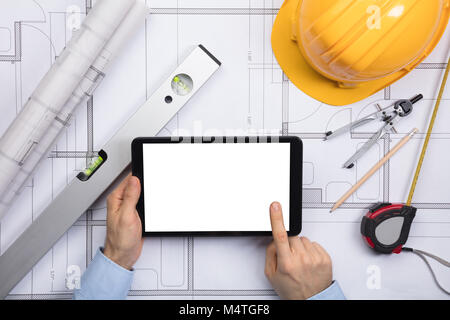 Architect drawing on a blueprint on screen over a white background close up of a male architect touching the screen of digital tablet on blueprint with malvernweather Gallery