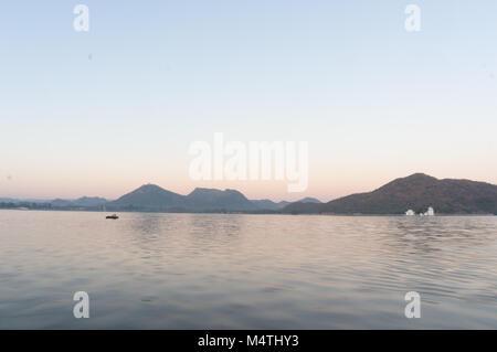 Serene dawn shot of Fateh sagar lake udiapur india. This famous tourist destination of India invites locals and - Stock Photo
