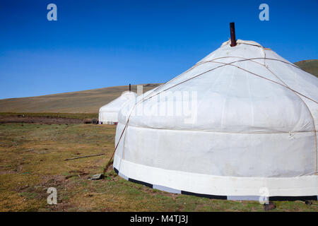 Traditional Mongolian portable round tent ger covered with white outer cover in Altai Mountains of Western Mongolia - Stock Photo
