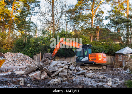 Construction site with orange heavy plant tracked mechanical excavator: remains of the demolition of a residential - Stock Photo