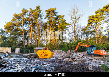 Construction site with orange heavy plant tracked mechanical excavator and skip: remains of demolition of a residential - Stock Photo