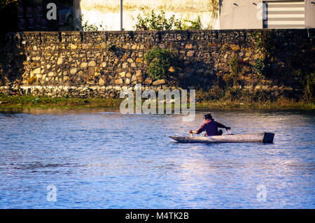 Udaipur, India - 25th Dec 2017: Fisherman on a rowing boat fishing in the shallow waters of lake fateh sagar. The - Stock Photo