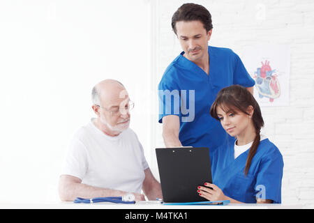 Happy senior patient and doctors in hospital - Stock Photo