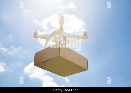 Low angle view of drone carrying parcel against sky on sunny day - Stock Photo